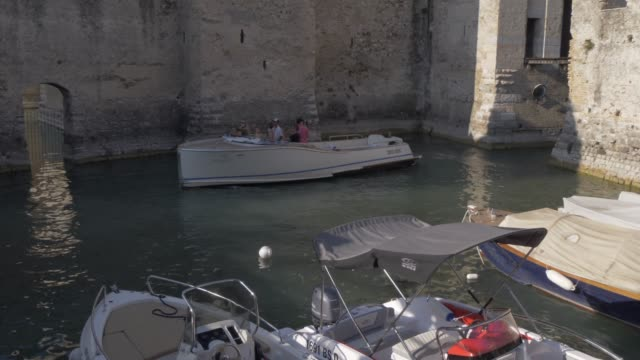 View of boat near ancient fortress Rocca Scaligera in Sirmione, Lake Garda, Lombardy, Italy, Europe