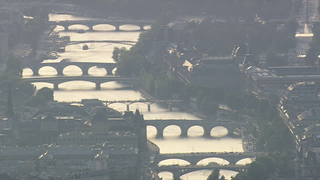 ms aerial td view of boat passing under bridges over seine backlit from east / paris, france - river seine stock videos & royalty-free footage