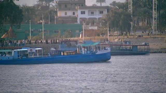 vídeos de stock e filmes b-roll de view of boats and a dock on the nile in luxor. - embarcação comercial
