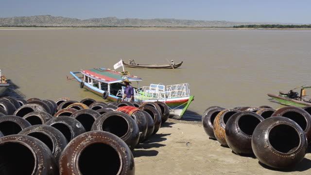 ws view of boats and large clay pots stored on banks of ayeyarwadi river for loading / bagan, mandalay division, myanmar - 帽子点の映像素材/bロール