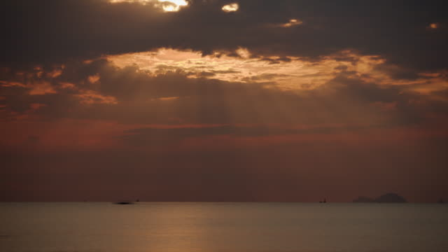 ws t/l view of boats and swimmers passing by in pink dawn as sunlight struggles to emerge from behind grey cloud / nha trang, vietnam - vietnam meridionale video stock e b–roll