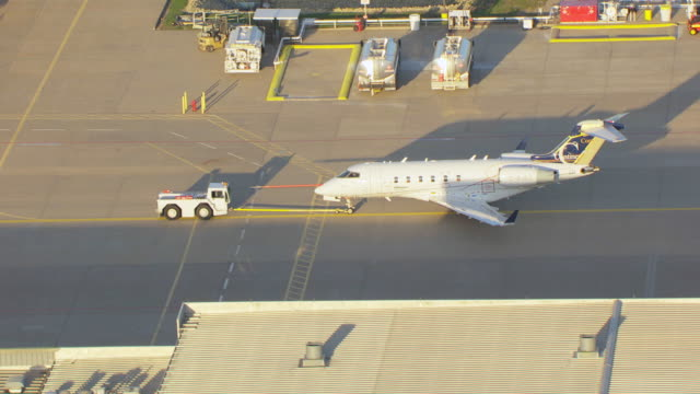 ms aerial zi view of bombardier learjet airplane being pulling on tarmac / wichita, kansas, united states - campo d'aviazione video stock e b–roll