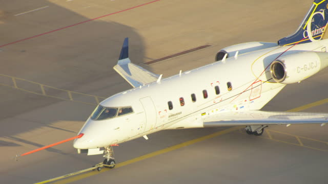 ms aerial zo ts view of bombardier learjet airplane being pulling on tarmac / wichita, kansas, united states - wichita stock-videos und b-roll-filmmaterial