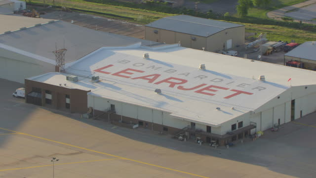 ms aerial zo view of bombardier learjet sign on hangar rooftop / wichita, kansas, united states - wichita stock-videos und b-roll-filmmaterial