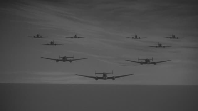 WS POV View of Bombers in flight FTC in formation coming toward, over land and sea Bombing raid, explosions going of below