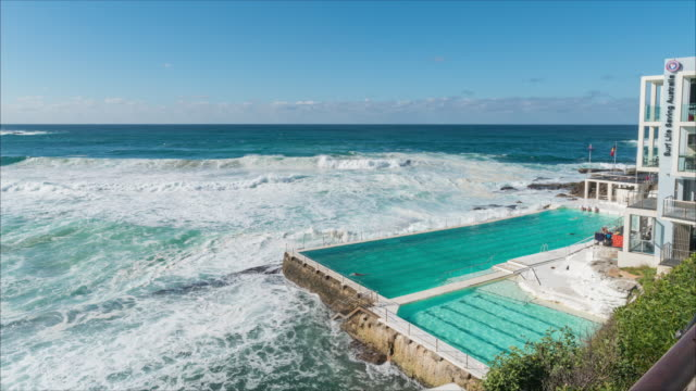 stockvideo's en b-roll-footage met view of bondi beach and bondi icebergs swimming pool (popular tourist attraction) - grote groep mensen