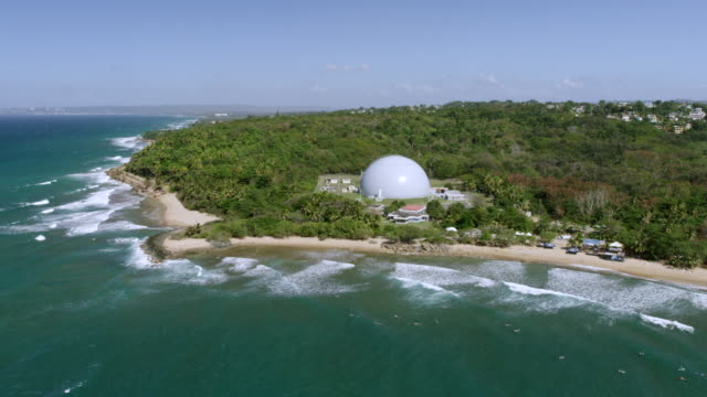 ws aerial pov view of bonus nuclear reactor and lighthouse, domes beach in foreground / rincon, puerto rico, united states  - nuclear reactor stock videos and b-roll footage