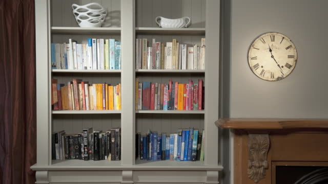 MS View of books in bookshelf, clock on wall / Auckland, North Island, New Zealand
