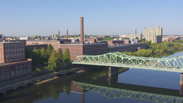 ws aerial pov view of boott cotton mills museum near by merrimack river and bridge / lowell, massachusetts, united states - lowell stock videos & royalty-free footage