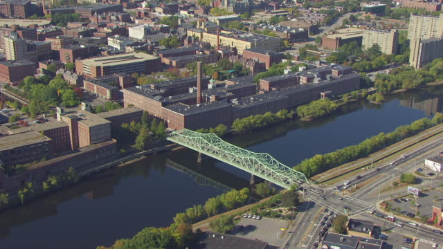 ws aerial pov view of boott cotton mills museum near by merrimack river over bridge / lowell, massachusetts, united states - lowell stock videos & royalty-free footage