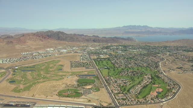 WS AERIAL View of Boulder City with patches of grass in desert conditions and lake with mountains surrounding city / Boulder City, Nevada, United States