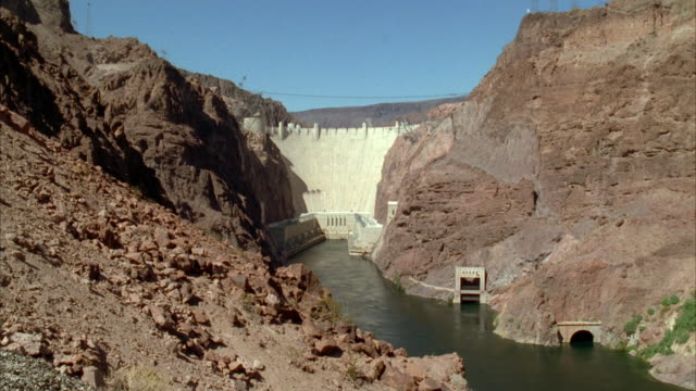 vídeos de stock, filmes e b-roll de ws pan view of boulder dam to buildings and churning water below / nevada, arizona, usa - represa hoover