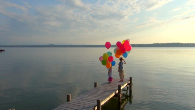 WS AERIAL View of boy and girl on pier let flying bunch of colorful balloons over lake / Ambach, Bavaria, Germany