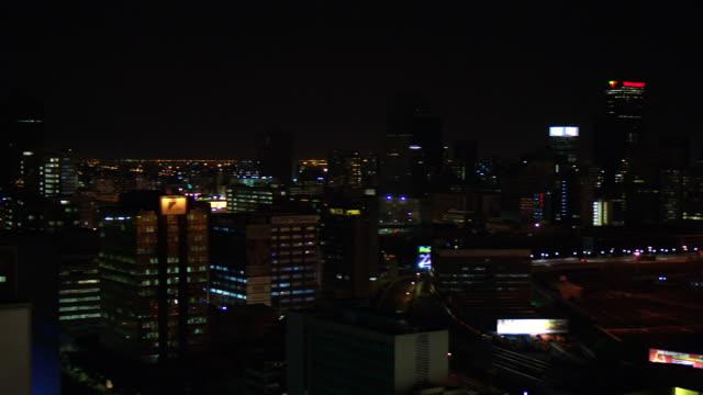 vídeos de stock e filmes b-roll de ws pan view of braamfontein and telkom tower to cbd with mandela bridge at night with colorful lights / johannesburg, gauteng, south africa - joanesburgo