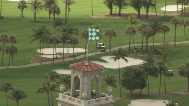 ws aerial zi view of breakers hotel and flag at top of hotel building with golf course in background / palm beach, florida, united states - golf flag stock videos and b-roll footage