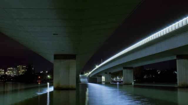 ws t/l zo view of bridge and freeway underpass with traffic, lights reflecting in water at night / canberra, australian capital territory, australia - canberra stock videos and b-roll footage