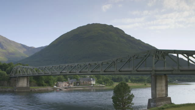 ws view of bridge crossing loch with ornate house and muntain in back side / ballachulish, scotland, united kingdom - loch点の映像素材/bロール