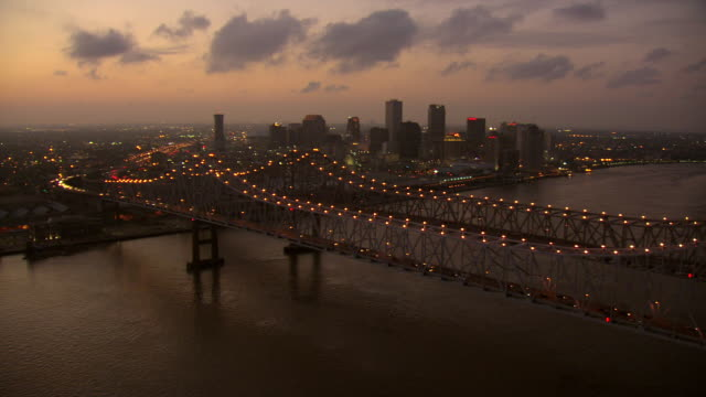 WS AERIAL View of bridge to reveal downtown buildings at sunset / New Orleans, Louisiana, United States