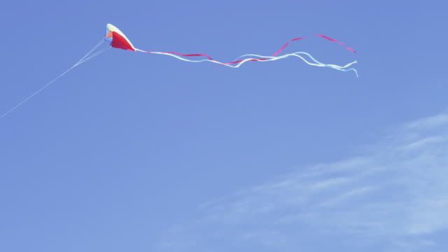 WS TS SLO MO View of brite multi color kite flies high in sky on sunny day / Astoria, Oregon, United States