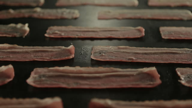view of broiling the rashers of bacon - grigliare video stock e b–roll