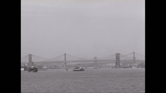 WS POV View of Brooklyn and Manhattan Bridges with boats moving in river / New York City, New York State, United States