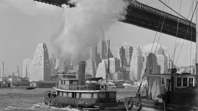 ws view of brooklyn bridge in foreground and city skyline in background with across east river boat enter foreground going away and other boats moving in water - brooklyn bridge stock videos & royalty-free footage