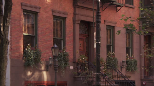 ws zo view of brownstone building side by street  / new york, new york,united states - yellow taxi video stock e b–roll