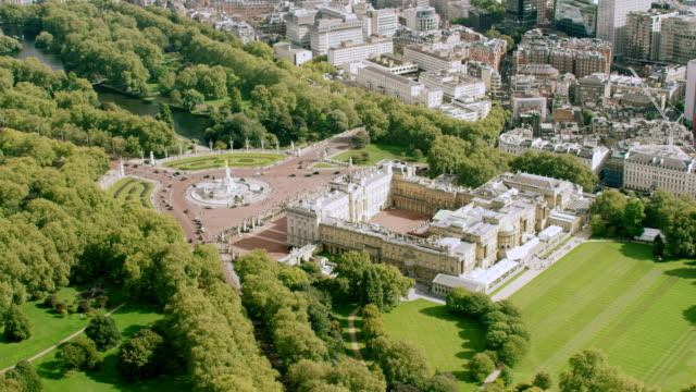 ws aerial pov view of buckingham palace and london eye with thames river palace in city / london, england, united kingdom - バッキンガム宮殿点の映像素材/bロール