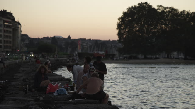ws view of building and people enjoying picnic near rhone river at dusk / geneva, switzerland - rhone river stock videos & royalty-free footage