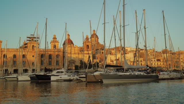 view of buildings and boats at harbor in valletta, malta - valletta stock videos & royalty-free footage