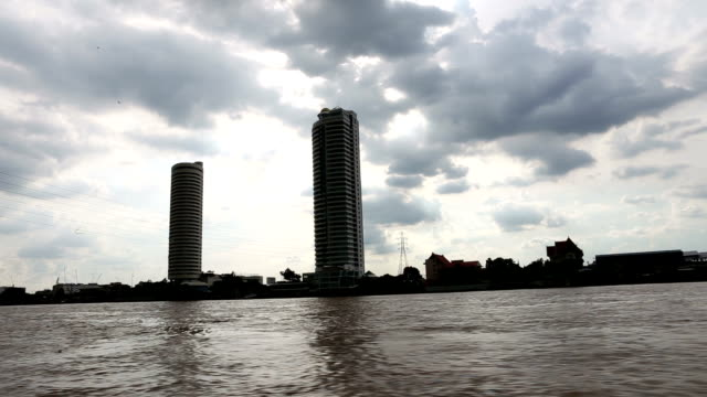view of buildings and sky in daytime along the chao phraya river. - river chao phraya stock videos & royalty-free footage