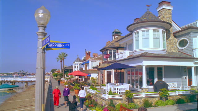 ws view of buildings and street light with sign in foreground / carona del mar, california, usa - 道路名の標識点の映像素材/bロール