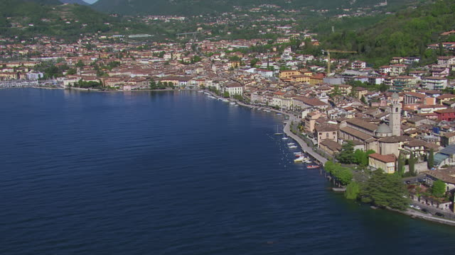 WS AERIAL View of buildings near lake and mountain / Lake Garda, Trentino, Verona, Brescia