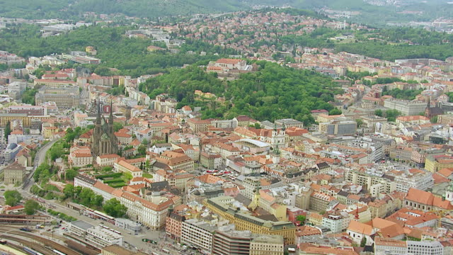 WS AERIAL View of buildings with trees and mountain / Brno, Brno City District, Czech Republic