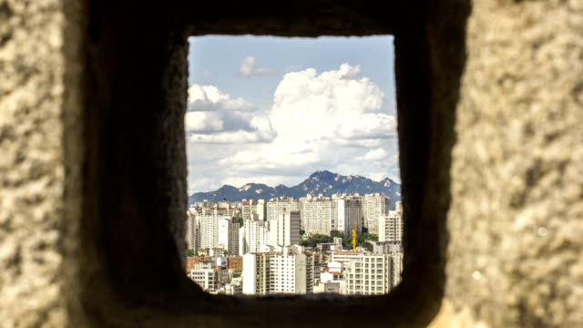 view of bukhansan mountain and cumulonimbus through the hole of seoul city wall (also called as hanyangdoseong and it's korea historic place 10) - 囲み塀点の映像素材/bロール