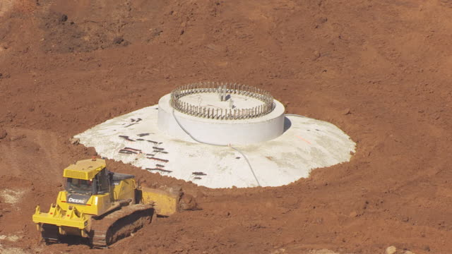 MS AERIAL DS View of bulldozer working at base of wind turbine generator at flat ridge wind farm in Harper County / Kansas, United States