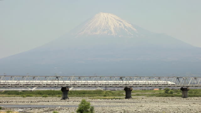 WS View of Bullet train Shinkansen passing on bridge in front of snow capped Mount Fuji / Fujigawa, Shizuoka Prefecture, Japan