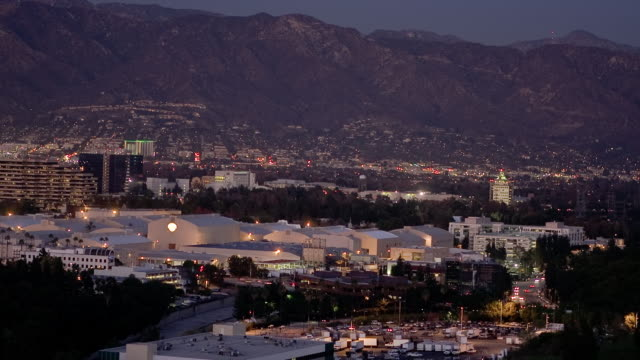 t/l, ws, ha, view of burbank with warner bros studio sound stages, mountains in background, dusk, universal city, california, usa - burbank stock-videos und b-roll-filmmaterial