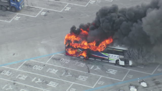 ws aerial zi zo view of bus on fire / mungyeong, gyeongsangbuk-do, south korea - ヘルメット類点の映像素材/bロール
