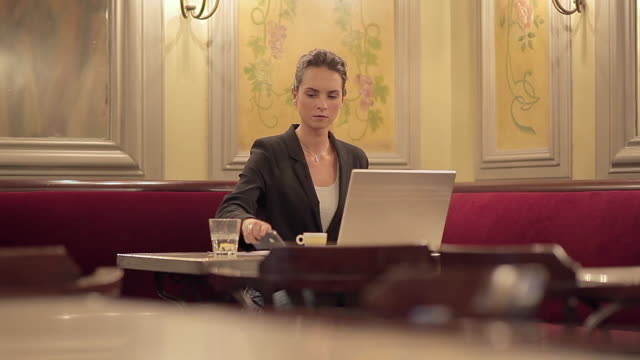 MS View of businesswoman in cafe working on laptop using phone and ordering more coffee / Toulouse, Haute Garonne, France