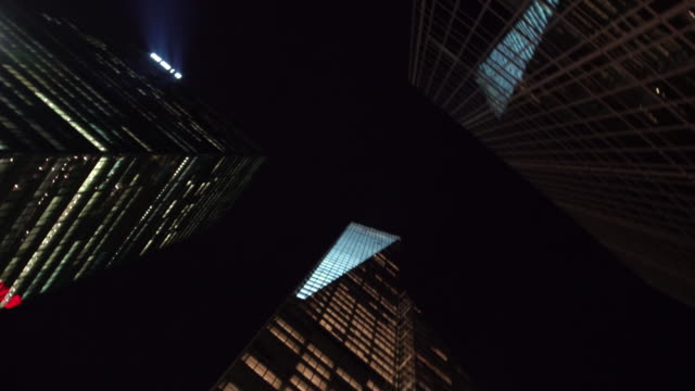 view of busy city street and towering skyscrapers at night - directly below stock videos & royalty-free footage