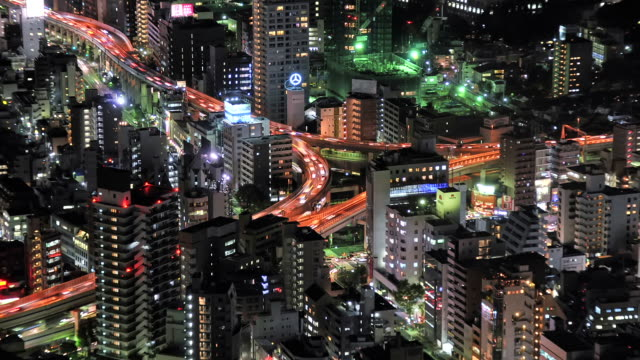 WS T/L View of busy elevated highway passing through high rise buildings at night / Tokyo, Japan