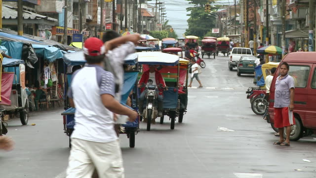 ws view of busy junction with lots of motorised rickshaws, people crossing, market stalls, parked mopeds and bustle / iquitos, peruvian amazon, peru - risciò video stock e b–roll