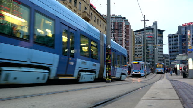 view of busy street in the center of oslo, norway with people, car, tram and bus road traffic during a cloudy autumn day. modern skyscrapers - tram stock videos & royalty-free footage