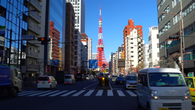 view of busy street with tokyo tower in the distance in tokyo, japan. - plusphoto stock videos & royalty-free footage