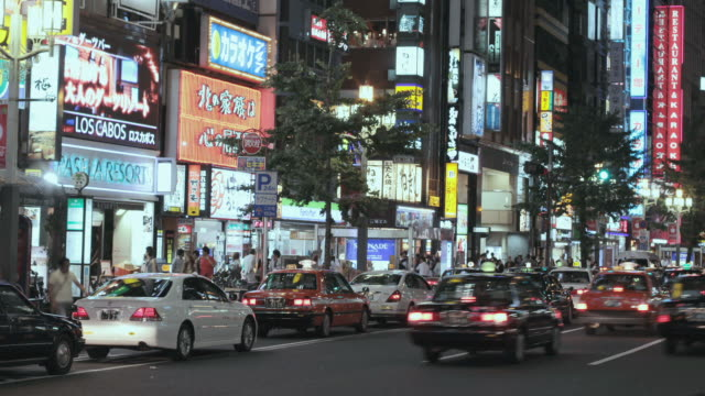 ws t/l view of busy street with traffic and neon signs near shinjuku station / shibuya, tokyo, japan - 電飾点の映像素材/bロール