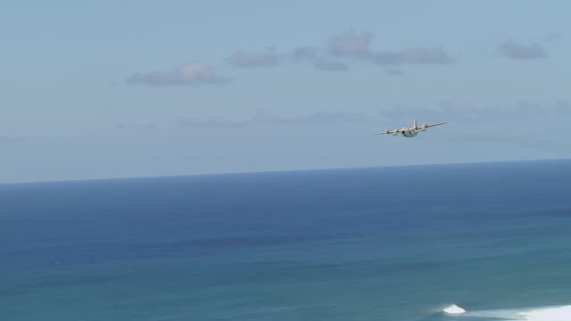 ws ts aerial view of c130 coast guard plane flying over ocean near island of oahu / hawaii, united states - coast guard stock videos & royalty-free footage