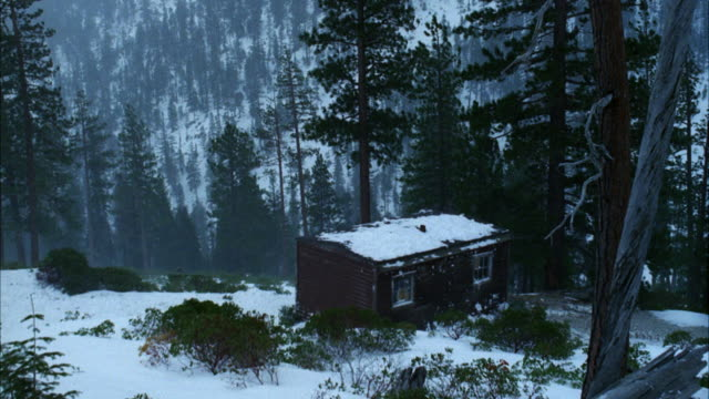 ms view of cabin in snow and snow covered mountains and trees. - 小屋点の映像素材/bロール