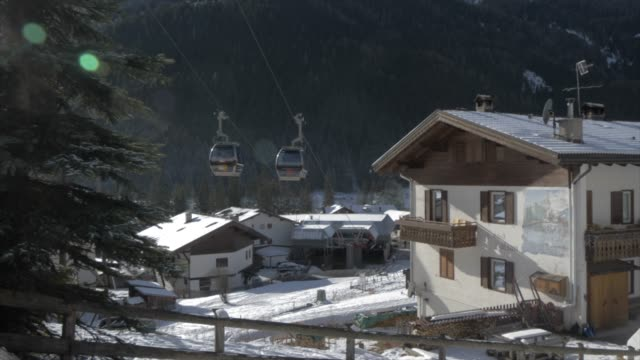view of cable cars and canazei town on sunny day in winter, province of trento, trentino-alto adige/sudtirol, italy, europe - canazei video stock e b–roll