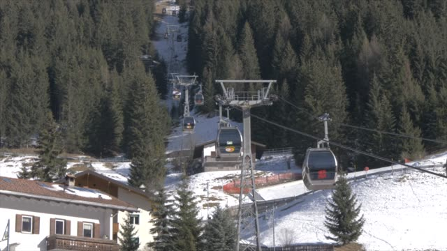 view of cable cars from canazei town centre on sunny day in winter, province of trento, trentino-alto adige/sudtirol, italy, europe - overhead cable car stock videos and b-roll footage